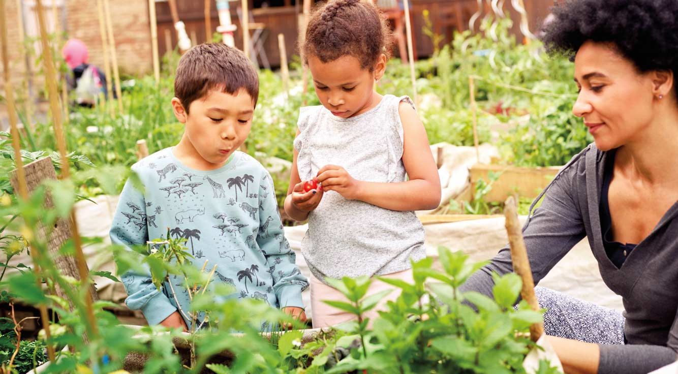 A woman and two small children visit a vegetable garden.