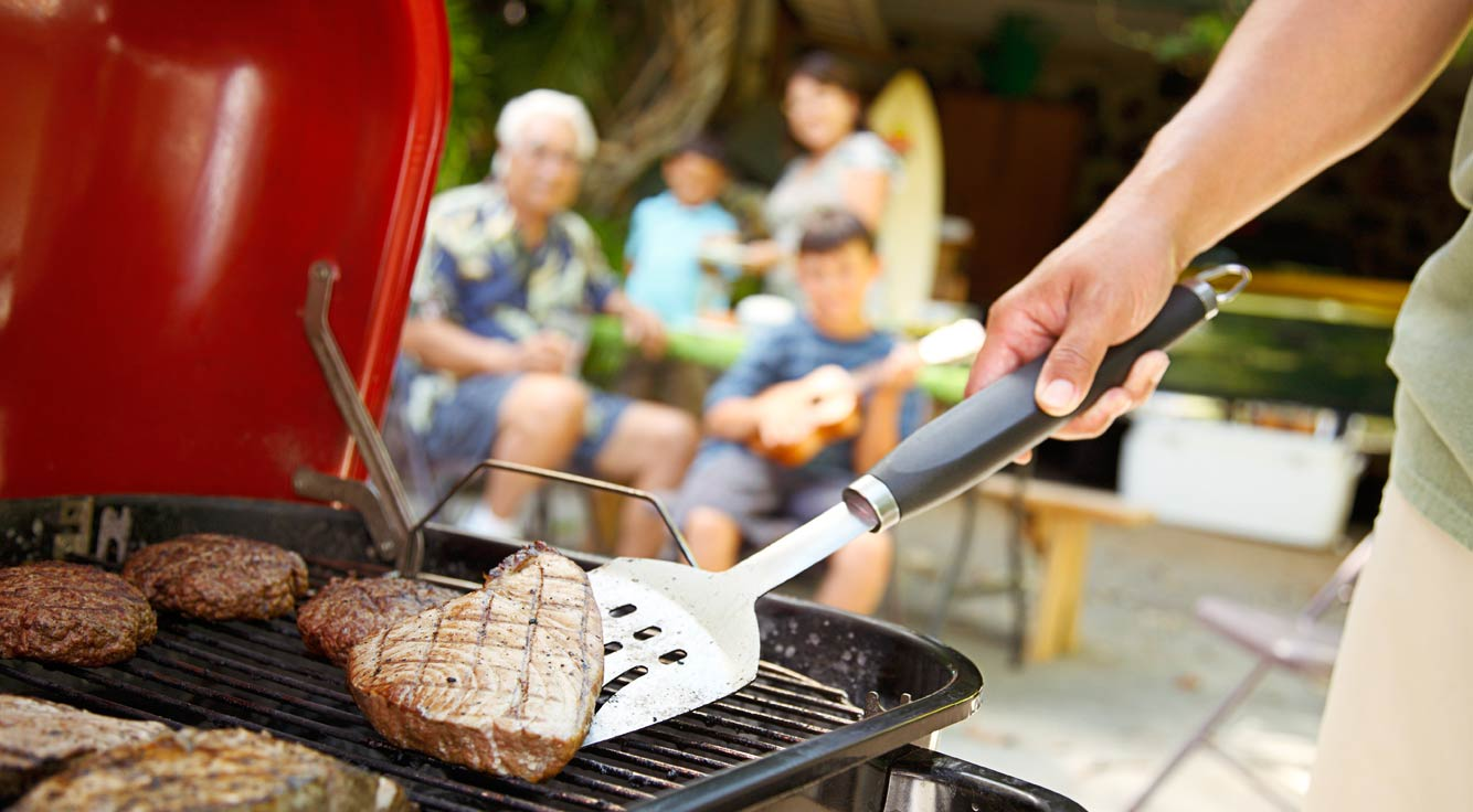A spatula flips meat on a grill.