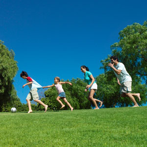 A family runs outside on a grassy field.