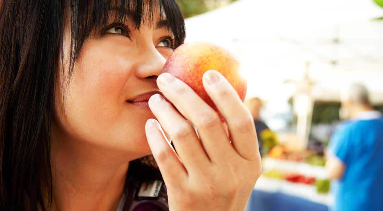 A young woman enjoys eating an apple outdoors.
