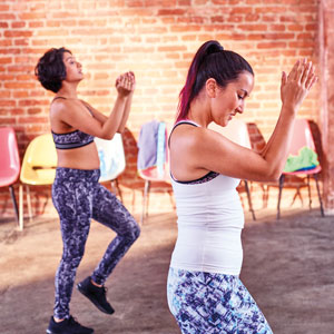 Two women in a fitness class clap their hands.