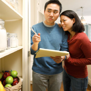 A man and woman take an inventory of their pantry.
