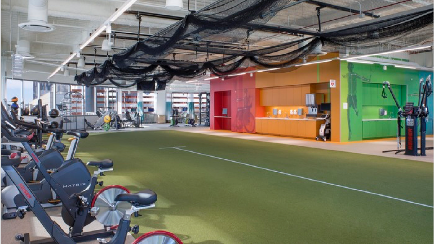 Comprehensive training and rehabilitation gym, with exercise bikes along the edge of a running turf with rainbow painted walls in the background