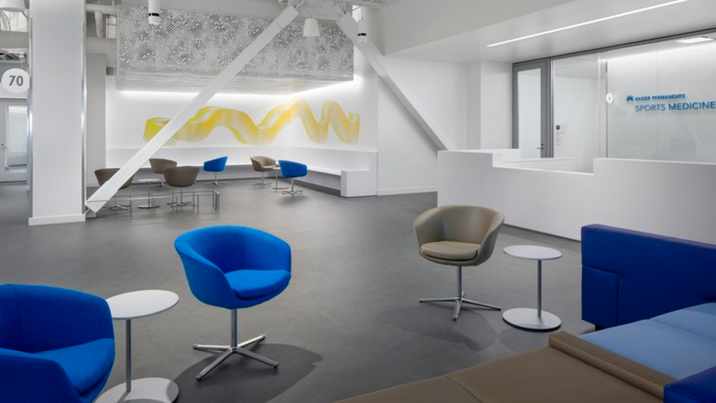 Modern, white dedicated reception and waiting area with blue and gray chairs