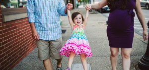 Kaiser Permanente image of a little girl in colorful dress swinging from hands of two adults